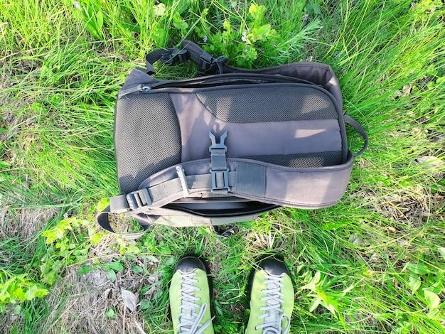 Tênis de turista e mochila na grama verde