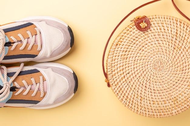 Tênis e bolsa de vime em fundo amarelo. conceito de viagens. camada plana - imagem