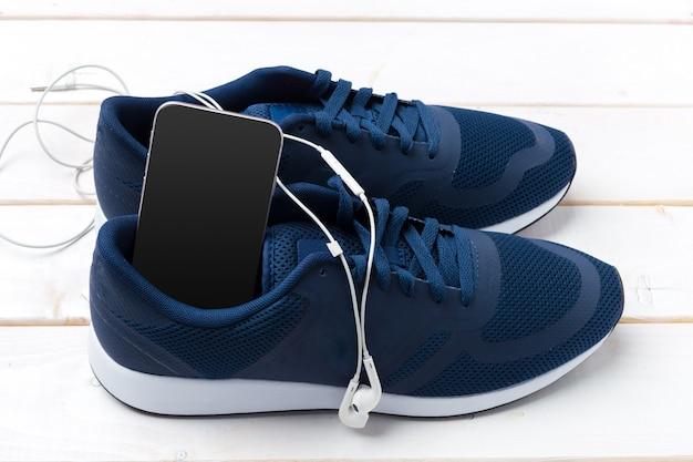 Tênis e celular com fones de ouvido