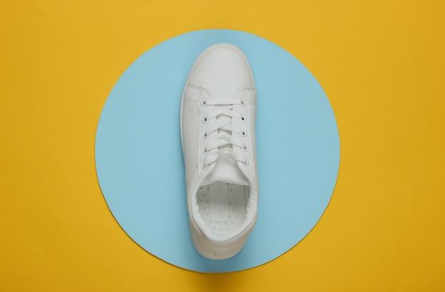 Tênis elegante branco em um amarelo com um círculo azul no meio