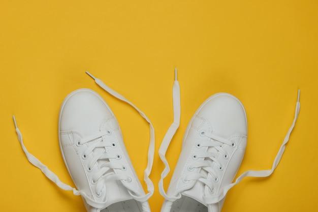 Tênis elegantes brancos com atacadores desamarrados em amarelo