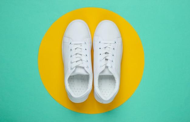 Tênis elegantes brancos em papel azul com círculo amarelo