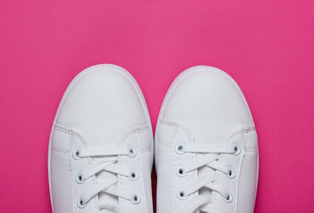 Tênis elegantes brancos em papel rosa com círculo rosa