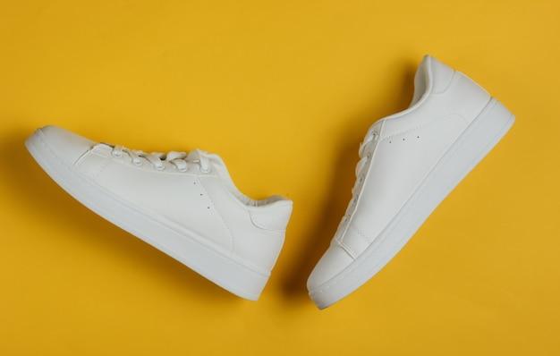 Tênis elegantes brancos em um amarelo