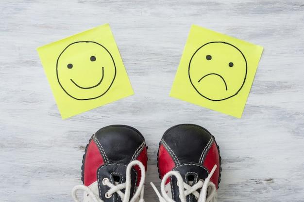 Tênis, escolha, mão desenhando smileys infelizes e felizes.