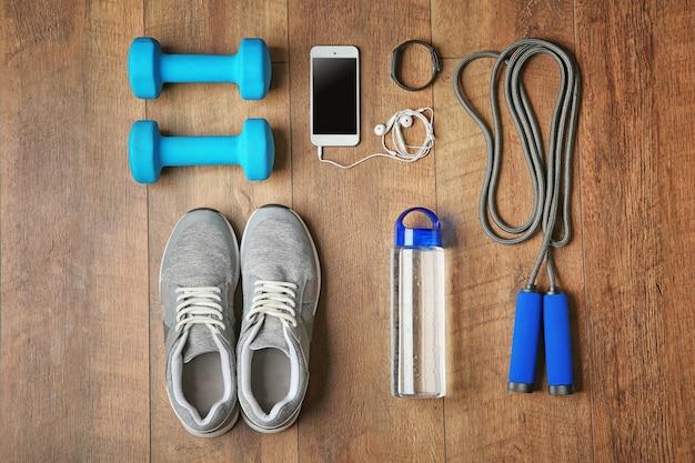 Tênis esportivos e equipamentos em fundo de madeira