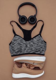 Tênis esportivos, top sutiã e fones de ouvido estéreo em fundo marrom. conceito de esporte e fitness. vista do topo. postura plana