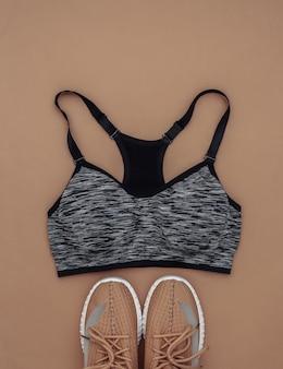 Tênis esportivos, top sutiã em fundo marrom. conceito de esporte e fitness. vista do topo. postura plana