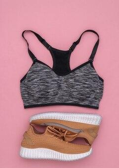 Tênis esportivos, top sutiã em fundo rosa. conceito de esporte e fitness. vista do topo. postura plana