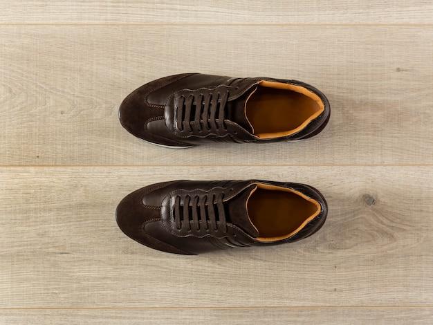 Tênis feitos de couro marrom genuíno ficam em uma vista de cima do piso claro