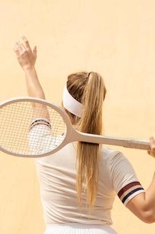 Tênis feminino joga de volta com raquete