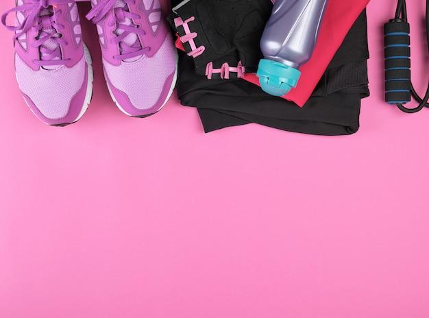 Tênis feminino rosa, garrafa de água, luvas e uma corda de pular para esportes
