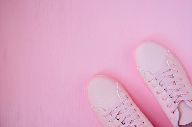 Tênis feminino rosa sobre fundo rosa. configuração plana, fundo mínimo, vista superior.