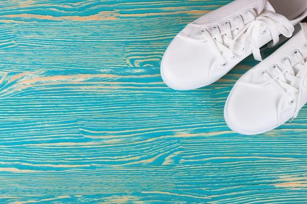 Tênis femininos brancos na mesa de madeira azul com espaço de cópia. vista de cima, configuração plana.