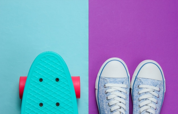 Tênis hipster e vista superior do skate no fundo azul roxo. conceito de moda do minimalismo.