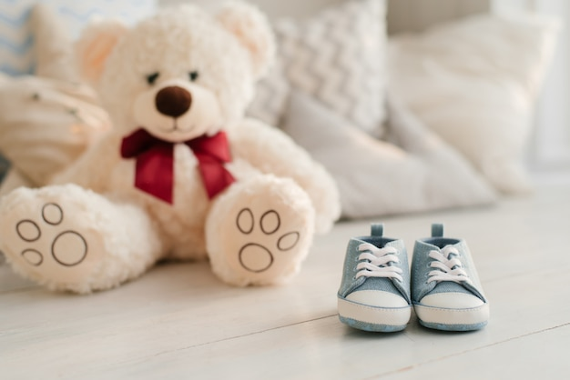 Tênis infantis azuis e brinquedos macios. o conceito de esperar um recém-nascido.
