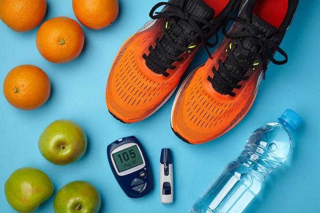 Tênis laranja, maçãs, laranjas e um medidor de glicose no sangue em um fundo azul. estilo de vida do diabetes. resistência a insulina