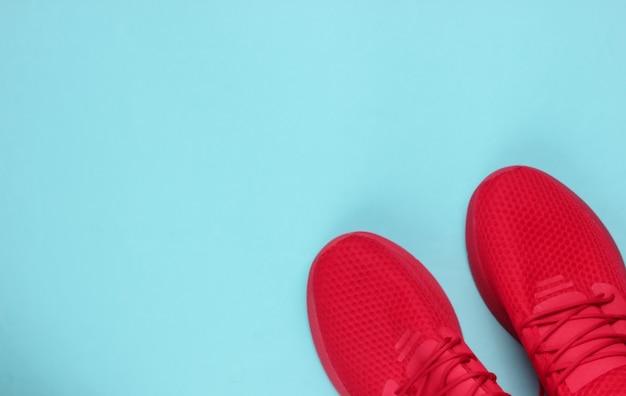 Tênis masculinos elegantes esportivos vermelhos para correr sobre fundo azul.