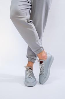 Tênis masculinos em um dia muito cinza de couro natural, sapatos masculinos com pernas em sapatos de couro cinza