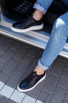 Tênis ou sapatos masculinos feitos de couro genuíno em close-up de pernas masculinas.