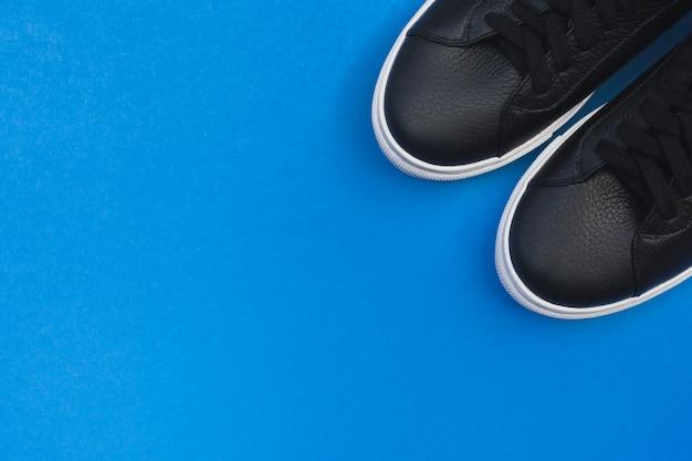 Tênis pretos sobre fundo azul. vista plana leiga, vista superior fundo mínimo.