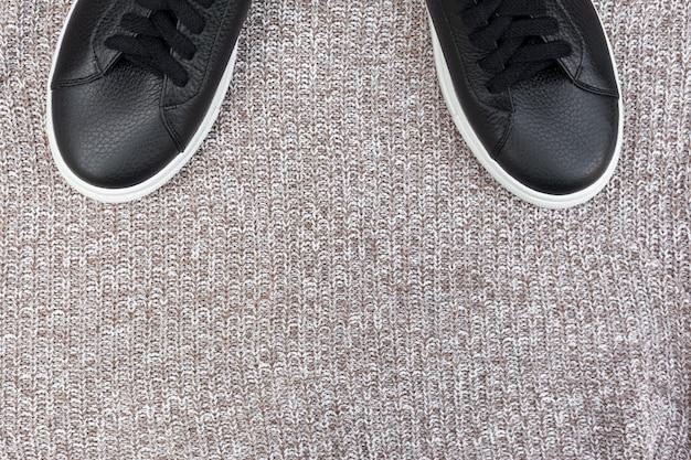 Tênis pretos sobre fundo de lã. vista plana leiga, superior. conceito de blog de moda. copie o espaço para texto