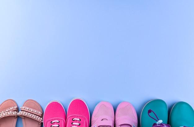 Tênis rosa, botas de borracha e sandálias para uma garota em um fundo azul. sapatos diferentes.