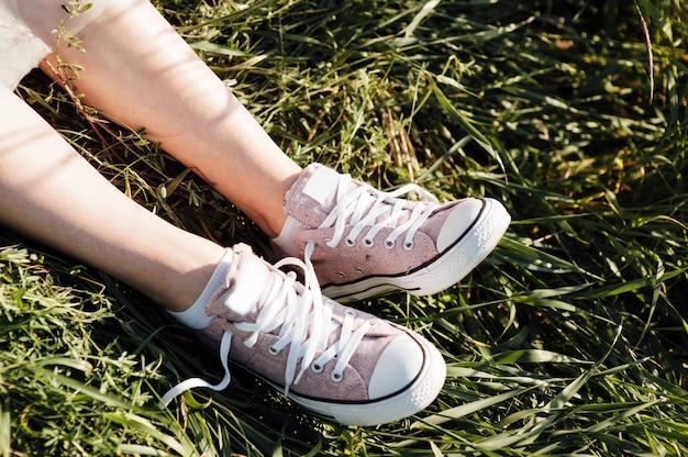 Tênis roxos nas pernas da garota na grama