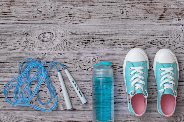 Tênis turquesa e uma corda de pular em alta velocidade sobre um piso de madeira. estilo esportivo. postura plana. a vista do topo.