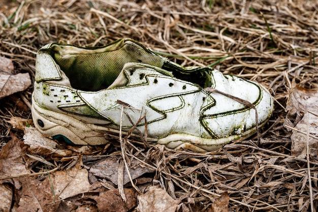 Tênis velhos e rasgados na grama suja.
