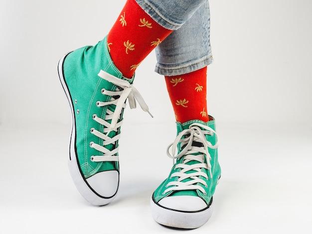 Tênis verdes elegantes e meias engraçadas em uma superfície branca. conceito de moda, beleza e bom humor