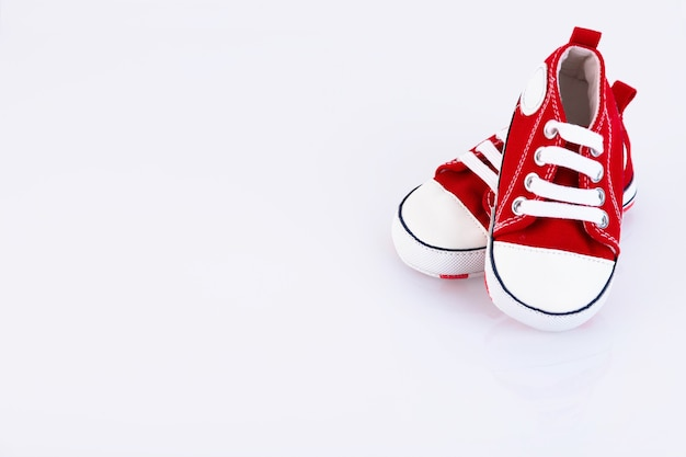 Tênis vermelho bebê isolado no fundo branco. loja de calçados infantis. copie o espaço.