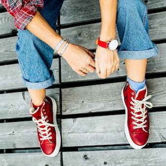 Tênis vermelhos elegantes na plataforma e roupas e acessórios da moda. estilo da cidade