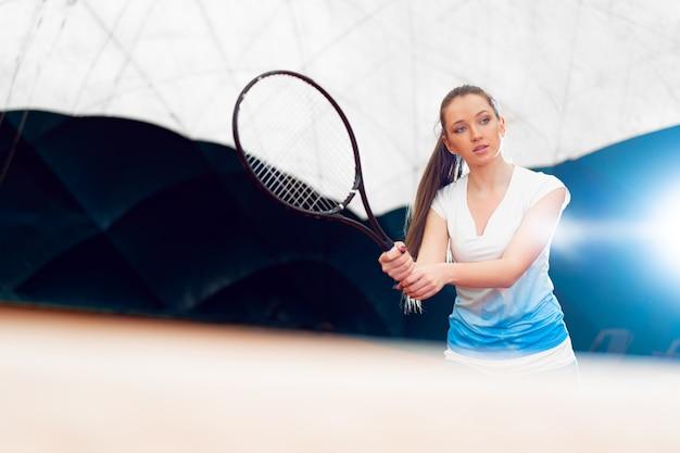 Tenista atraente, esperando pelo serviço na quadra coberta