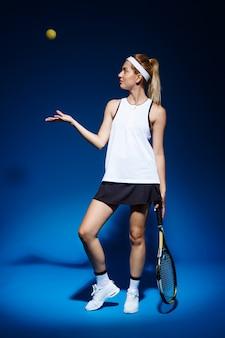 Tenista com raquete e bola posando