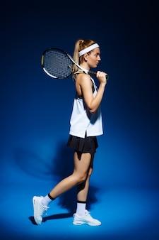 Tenista com raquete no ombro posando