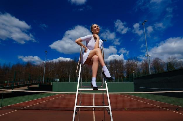 Tenista garota sexy em vestido branco e salto alto, segurando a raquete de tênis na quadra. jovem está jogando tênis, esporte