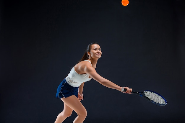 Tenista linda garota com uma raquete em fundo escuro