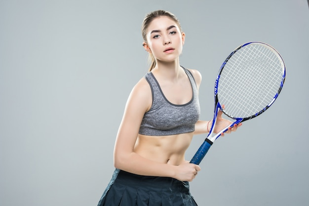 Tenista linda garota com uma raquete na parede branca isolada. anúncio de tênis.