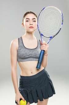 Tenista mulher confiante segurando raquete e bola isolada sobre parede cinza