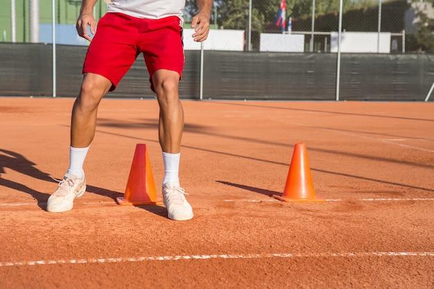 Tenista profissional aquecendo esquivando-se de cones em zigue-zague.