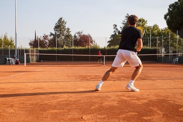 Tenista profissional jogando tênis em uma quadra de tênis de saibro em um dia ensolarado.