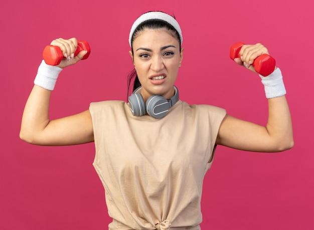 Tensa, jovem, caucasiana, esportiva, usando fita para a cabeça e pulseiras com fones de ouvido ao redor do pescoço, olhando para a frente, levantando halteres isolados na parede rosa