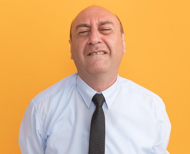 Tenso, com olhos fechados, homem de meia-idade vestindo camiseta branca com gravata isolada na parede laranja