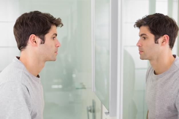 Tenso homem olhando para si mesmo no espelho do banheiro