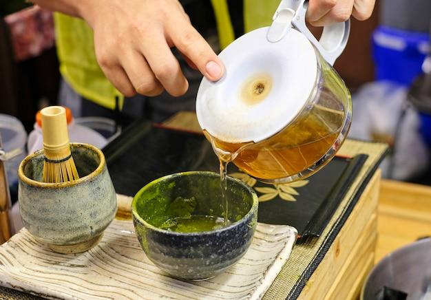 Tentando derramar água quente formar jarros de vidro em uma tigela preta que contém chá verde matcha