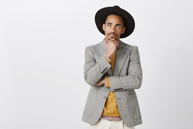 Tentando encontrar solução, tornar a vida melhor. homem africano atraente focado em roupas elegantes e chapéu preto, tocando o queixo, olhando para cima com expressão pensativa, pensando ou relembrando eventos importantes