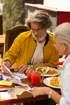 Tentando lembrar. homem barbudo concentrado sentado com sua esposa no café e olhando as fotografias impressas.