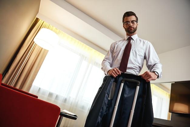 Tentando não amassar a jaqueta. homem de negócios de óculos leva sua jaqueta para uma mala perto de um sofá vermelho em um quarto de hotel
