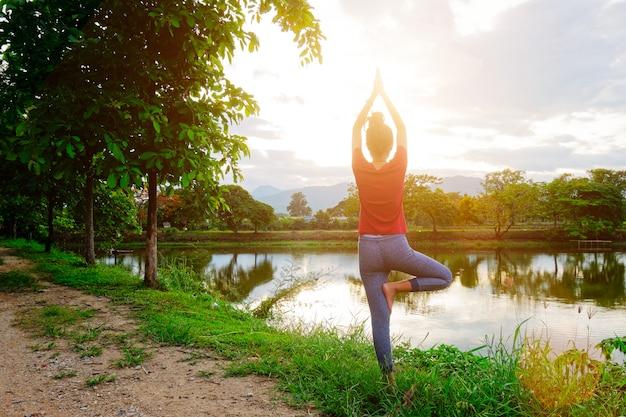 Tentativa da menina a ioga da pose da árvore